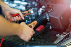 Механик используя соединительные кабели для того чтобы начать автомобиль Стоковые Фотографии RF