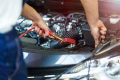 Механик используя соединительные кабели для того чтобы начать автомобиль Стоковое Изображение RF