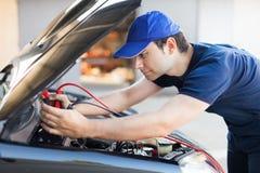 Механик используя кабели к запуску двигатель автомобиля стоковые фото