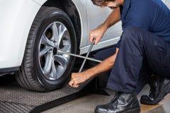 Механик используя ключ оправы для того чтобы исправить автошина автомобиля Стоковые Изображения