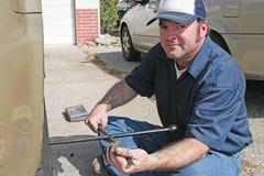 Механик используя утюг автошины Стоковая Фотография