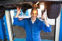 Механик используя факел для того чтобы посмотреть под автомобилем Стоковое Изображение RF