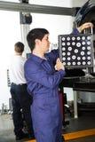 Механик используя Aligner колеса на автомобиле в гараже Стоковое Изображение RF