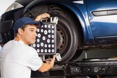 Механик используя Aligner колеса на автомобиле на гараже Стоковое Изображение RF