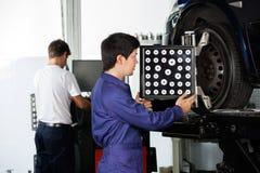 Механик используя Aligner колеса на автомобиле Стоковое Изображение RF