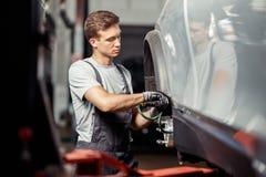 Механик исправляет поднятый автомобиль стоковое фото rf