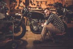 Механик и винтажный мотоцикл каф-гонщика стиля Стоковая Фотография