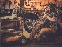 Механик и винтажный мотоцикл каф-гонщика стиля Стоковое Фото