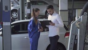 Механик милой девушки автоматический принимая подписанные данные об автомобиле и принимающ ключ и трясущ руку молодого красивого  видеоматериал