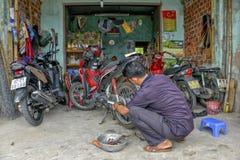Механик мотоцикла ремонтируя самокат спущенной шины стоковое изображение