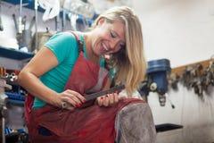 Механик молодой женщины храня ее ногти с большим файлом металла Стоковые Фото