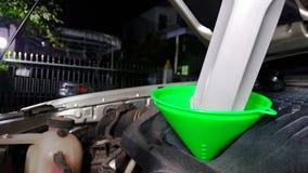 Механик обслуживать обслуживания автомобиля лить новую смазку масла в двигатель автомобиля стоковое изображение