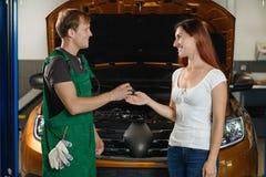 Механик передает ключи автомобиля к клиенту в руках стоковые фотографии rf