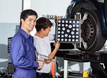 Механик при коллега используя Aligner колеса на автомобиле Стоковое Фото