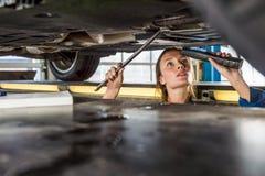Механик при электрофонарь ремонтируя автомобиль на гидравлическом подъеме стоковые фото