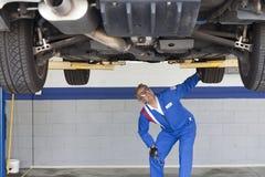 Механик проверяя автомобиль на ремонтной мастерской автомобиля Стоковое фото RF