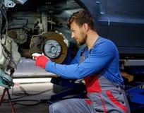 Механик проверяя тормозную систему автомобиля стоковое изображение