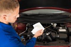 Механик проверяя уровень масла в двигателе автомобиля Стоковые Изображения RF