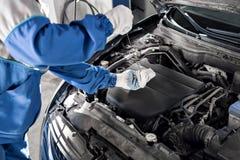 Механик проверяя уровень масла в мастерской автомобиля Стоковые Фото