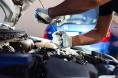 Механик работая в гараже ремонта автомобилей Обслуживание автомобиля Стоковая Фотография
