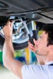 Механик работая в мастерской автомобиля Стоковые Фотографии RF