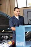 Механик работая на автомобиле стоковое фото