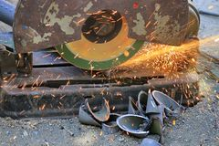 Механик режет сталь с машиной с много искрами стоковая фотография