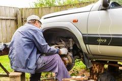 Механик ремонтирует передний подвес автомобиля дома стоковая фотография