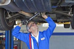 Механик ремонтируя автомобиль с универсальным гаечным ключом Стоковые Фотографии RF