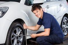 Механик ремонтируя автошину автомобиля с ключем оправы Стоковое Фото