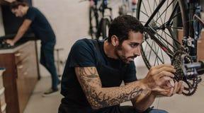 Механик ремонтируя велосипед в мастерской Стоковые Изображения