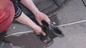 Механик ремонтируя колесо тележки видеоматериал