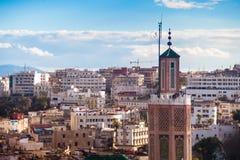 Мечеть в старом Medina с современными зданиями города на заднем плане стоковые изображения