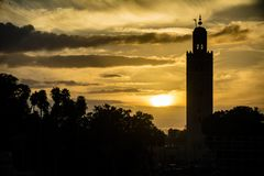 Мечеть Marrakesh в силуэте на заходе солнца в Марокко стоковое изображение rf