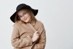 Мечтательная довольная положительная молодая женщина в ретро пальто и шляпе, нося стильных eyeglasses, обручах в пальто, стоит пр Стоковые Изображения RF