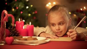 Мечтательная маленькая девочка думая над ее желаниями к Санта, писать письмо, детство стоковая фотография
