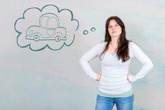 Мечтательная молодая женщина желая купить новый автомобиль символизированный автомобилем внутри стоковое изображение