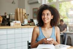 Мечтательный красивый студент девушки сидя в кафе при книги и кассеты усмехаясь держащ думать телефона Стоковые Изображения