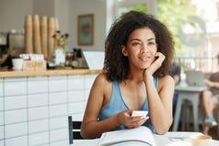 Мечтательный красивый студент девушки сидя в кафе при книги и кассеты усмехаясь держащ думать телефона Стоковое фото RF