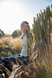 Мечтательная девушка сидя на утесе Стоковая Фотография