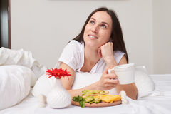 Мечтательное усмехаясь брюнет наслаждаясь ее незабываемым завтраком Стоковые Фото