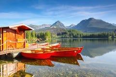 Мечтательные красные шлюпки стоят на пристани на тихом озере Стоковые Изображения RF