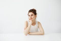 Мечтательный молодой красивый студент девушки сидя на таблице мечтая думать над белой предпосылкой Стоковая Фотография RF