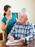 Мечтательный старший человек заполняет внутри вопросник Стоковые Фото