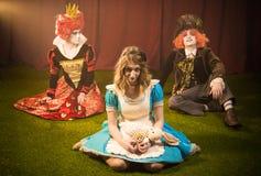 Мечтательный hatter и серьезная Алиса с ферзем стоковые изображения