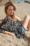 Мечтать красивая девушка сидя на больших камнях Стоковое фото RF