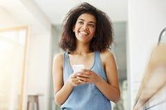 Мечтать мечтательной красивой африканской девушки усмехаясь думая держащ телефон сидя в кафе Стоковое Изображение RF