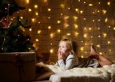 Мечтать молодого ребёнка лежа около волшебных подарков ремесла Нового Года рождественской елкой Стоковые Изображения RF