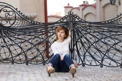 Мечтающ женщина сидя вниз снаружи Стоковое Фото