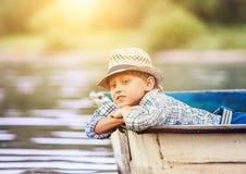 Мечтая мальчик лежа в старой шлюпке на реке Стоковые Фотографии RF
